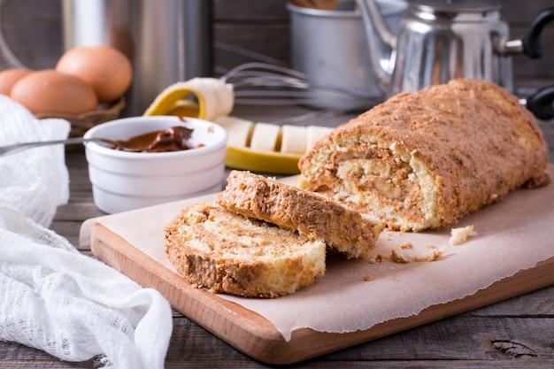 Rolinho de biscoito doce caseiro com creme e banana em uma mesa de madeira