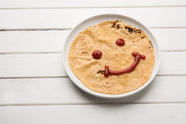 Rolinho de chapati com ketchup de tomate ou geléia de geléia de fruta com rosto sorridente, cardápio de comida favorita de crianças indianas para caixa de tiffin escolar, foco seletivo