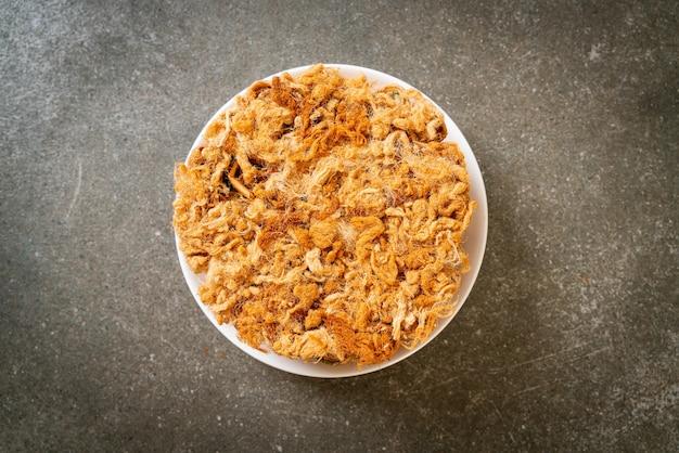Rolinho de coco crocante com carne de porco desfiada seca no prato
