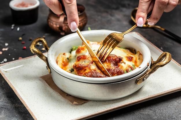 Rolinho de crepes de espinafre quente assado com frango, queijo, cogumelos e molho bechamel. fundo de receita de comida. fechar-se.