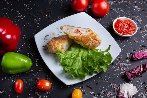 Rolinho de frango com molho vermelho, preto com tomate vermelho, pão, pimentão verde vermelho e brócolis