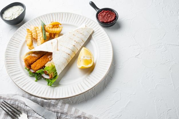 Rolinho de peixe e molho tártaro definido, no prato, na mesa branca