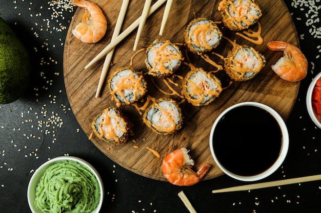 Rolinho de salmão com arroz, molho de soja, gergelim, gengibre e wasabi