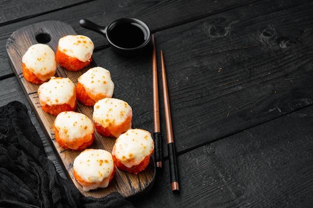 Rolinho de sushi assado com tampa de caviar de camarão e masago. conjunto de prato de restaurante de sushi tradicional, no fundo preto da mesa de madeira, com copyspace e espaço para texto
