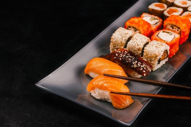 Rolinho de sushi com pauzinhos em uma bandeja em um fundo preto
