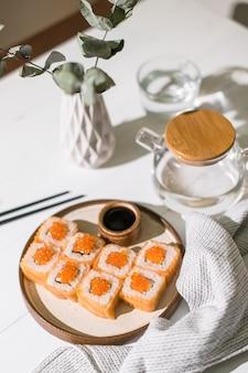 Rolinho de sushi com salmão e caviar. comida japonesa. rolinhos de salmão e caviar servidos em fundo branco de madeira
