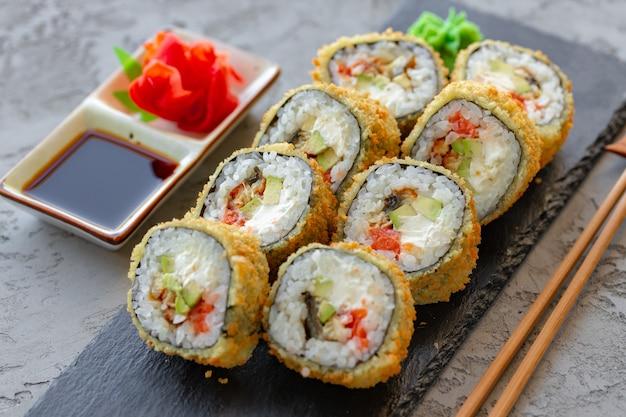 Rolinho de tempura de sushi japonês servido em prato de pedra preta