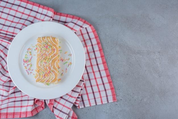Rolinho doce com sabor de baunilha decorado com granulado em prato branco.