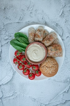 Rolinho primavera com carne e legumes, servidos em um prato branco com molho