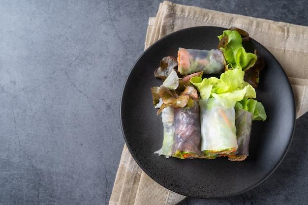 Rolinho primavera de vegetais frescos, alimentos limpos, salada para perda de peso, em fundo escuro