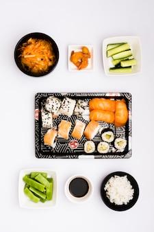 Rolinhos asiáticos deliciosos; salada; camarão frito; fatias de abobrinha; arroz cozido no vapor com molho de soja e feijões planos sobre o fundo branco
