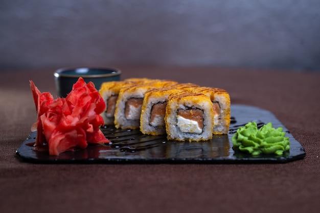Rolinhos assados com salmão e queijo em uma bandeja preta.