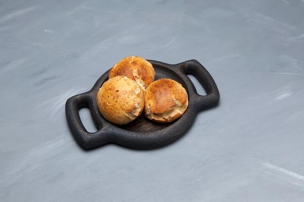 Rolinhos caseiros com queijo no prato de madeira. pastéis sem glúten.