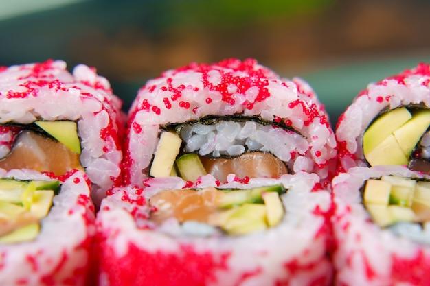 Rolinhos da califórnia com caviar, salmão e abacate, pepino e close-up de nori.