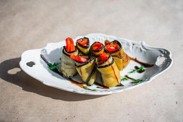 Rolinhos de berinjela assada com frango, cebolas e cenouras em um prato closeup