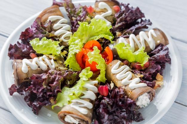 Rolinhos de berinjela com queijo, alho e molho branco e folhas de salada de alface