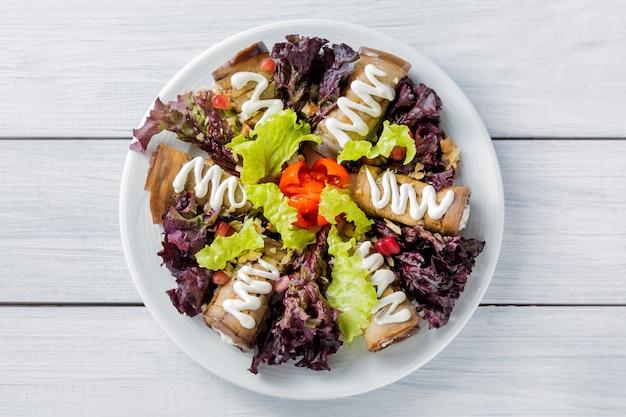 Rolinhos de berinjela com queijo, alho e molho branco e salada de alface folhas na chapa branca e mesa de madeira