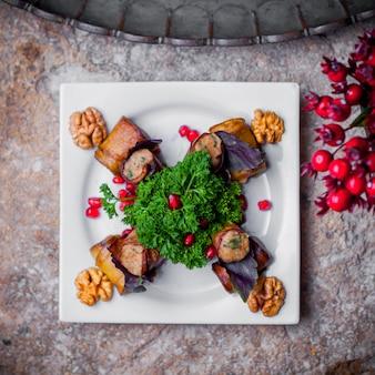 Rolinhos de berinjela de salada de vista superior com sementes de romã e verdes em chapa branca