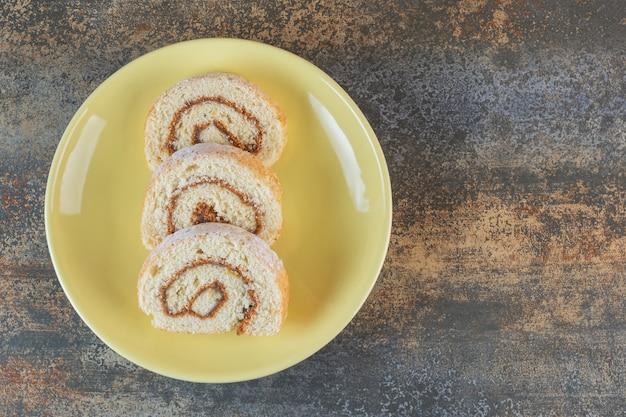 Rolinhos de bolo caseiro em prato amarelo