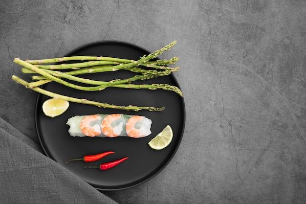 Rolinhos de camarão e aspargos no prato com molho