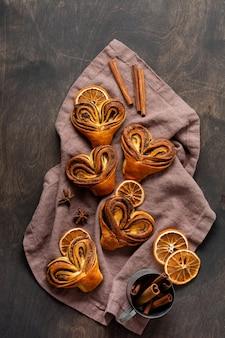 Rolinhos de canela caseiros doces em forma de coração em um antigo estilo retrô. humor de ano novo.