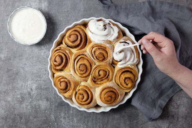 Rolinhos de canela, pãezinhos em uma assadeira com açúcar mascavo, molho de creme de requeijão e paus de canela com mão feminina enfeitam pães com creme.