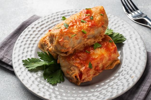 Rolinhos de couve com carne, arroz e legumes no prato. folhas de couve recheada com carne. mesa de concreto cinza