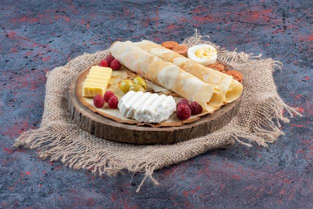 Rolinhos de crepe com linguiça, ovo, queijo e manteiga.