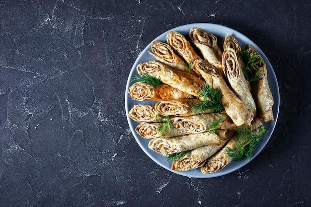 Rolinhos de crepe de trigo sarraceno com carne, vegetais e cogumelos em um prato sobre uma mesa de concreto, vista de cima, camada plana