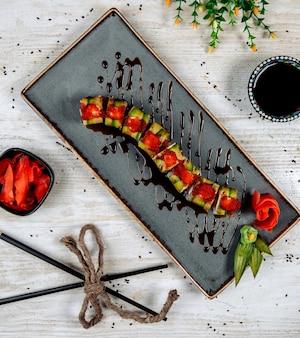 Rolinhos de dragão com abacate coberto com tobiko vermelho e molho de soja