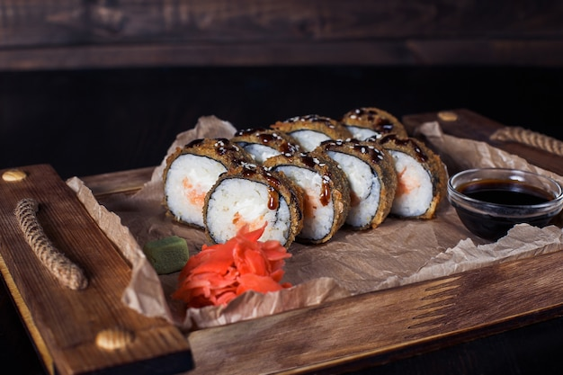Rolinhos de frutos do mar em uma bandeja de madeira, bela porção, superfície escura.