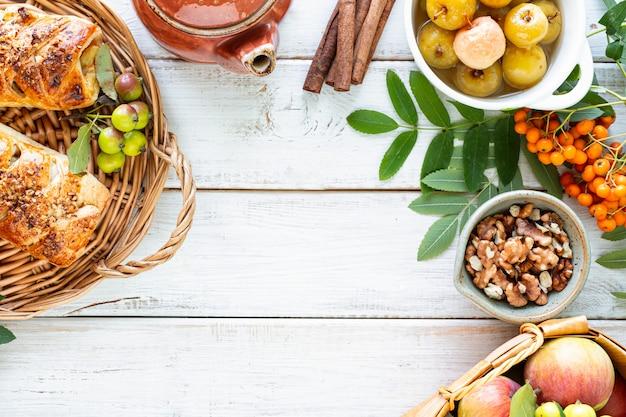 Rolinhos de maçã e canela recém-assados feitos de massa folhada em uma mesa de madeira branca