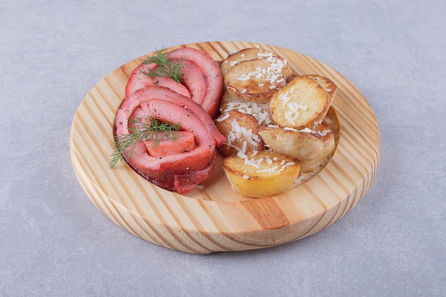 Rolinhos de presunto e batatas fritas em um pedaço de madeira.
