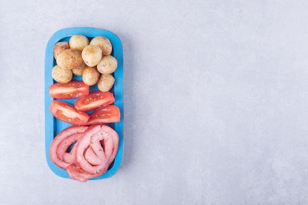 Rolinhos de presunto, tomate e batatas fritas na placa azul.