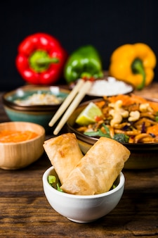 Rolinhos de primavera frito em tigela branca com comida tailandesa na mesa de madeira