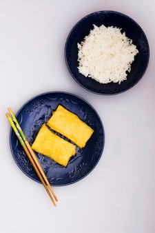 Rolinhos de primavera frito na chapa com pauzinhos perto de arroz cozido no vapor sobre o pano de fundo branco