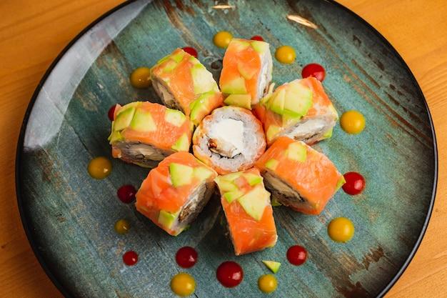 Rolinhos de salmão e enguia frescos com abacate, servidos em um prato azul