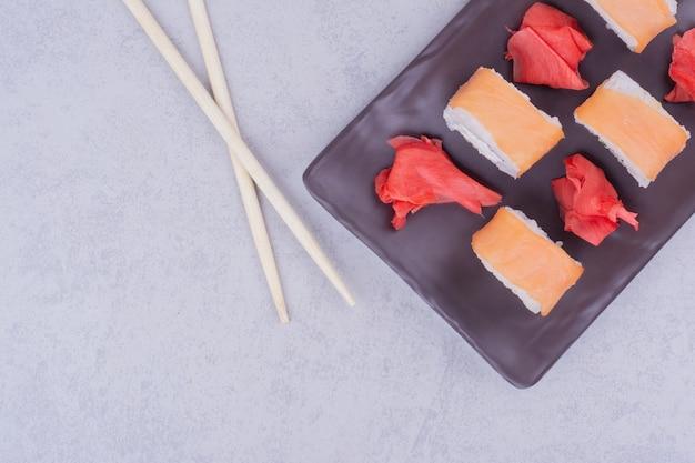 Rolinhos de salmão e gengibre vermelho marinado em uma travessa preta.