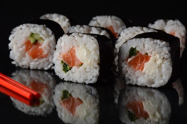 Rolinhos de salmão ou maki-zushi. com nigirizushi, em fundo preto com reflexo