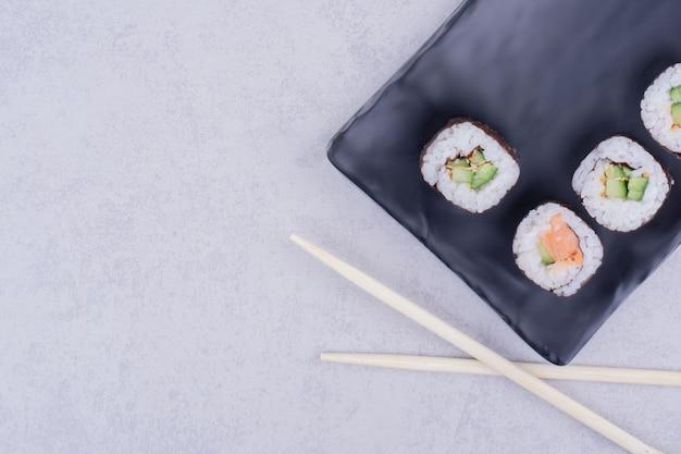 Rolinhos de saquê maki com salmão e abacate em uma travessa de cerâmica preta
