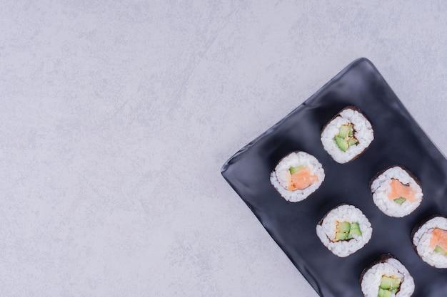 Rolinhos de saquê maki com salmão e abacate na travessa preta.