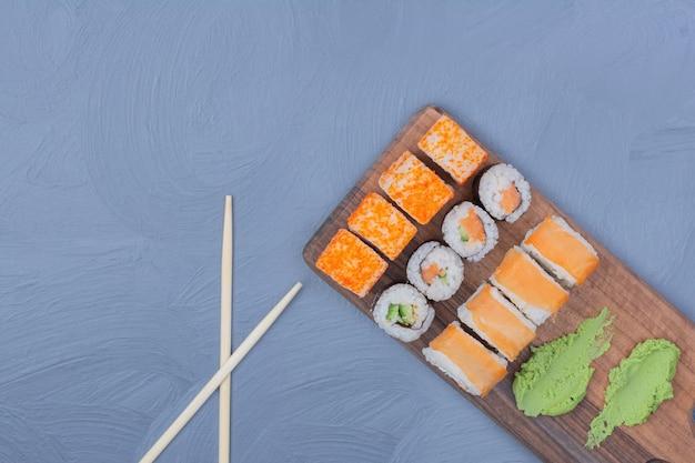 Rolinhos de saquê maki e philadelphia com molho de wasabi em uma travessa de madeira
