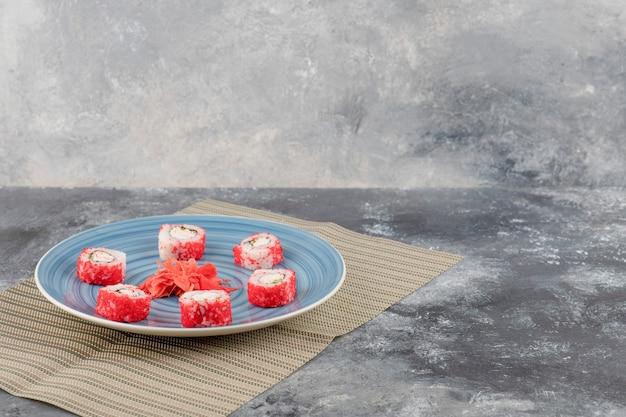 Rolinhos de sushi californianos e gengibre em conserva em prato azul