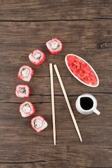 Rolinhos de sushi californianos, gengibre em conserva e molho de soja em superfície de madeira