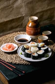Rolinhos de sushi caseiros com salmão, omelete japonesa, avacado, gengibre e molho de soja com pauzinhos no guardanapo de palha sobre a mesa de madeira balck. conjunto de saquê de bebida de cerâmica. jantar estilo japonês