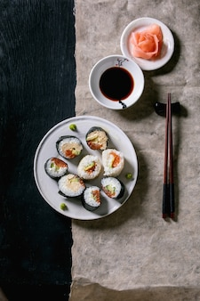 Rolinhos de sushi caseiros com salmão, omelete japonesa, avacado, gengibre, wasabi e molho de soja com pauzinhos em papel cinza sobre fundo preto de madeira. vista superior, configuração plana. jantar estilo japonês