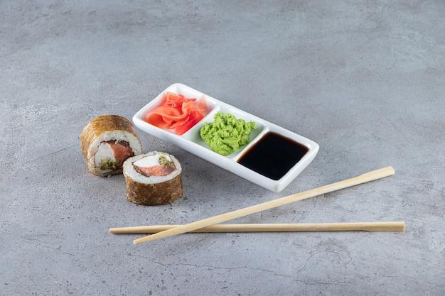 Rolinhos de sushi com atum, wasabi, gengibre e molho de soja em fundo de pedra.