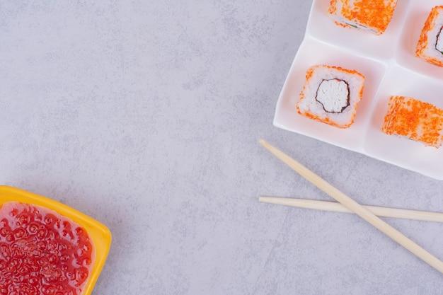 Rolinhos de sushi com caviar vermelho, cream cheese e molho de pimenta doce.