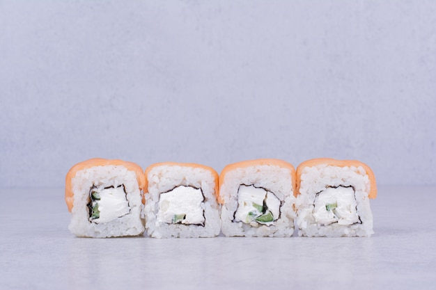 Rolinhos de sushi com cream cheese em fundo cinza