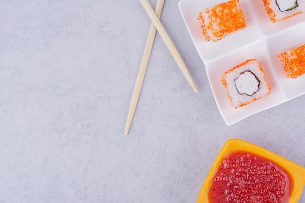 Rolinhos de sushi com cream cheese em uma travessa branca com molho de pimenta doce